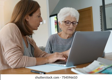 Elderly woman using laptop with help of homecarer