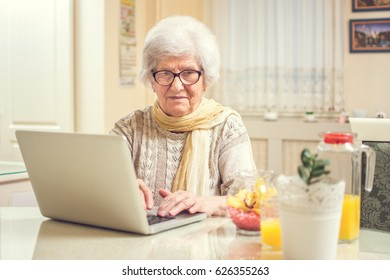 Elderly woman using laptop at home.