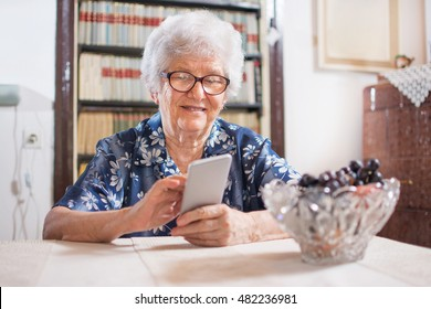 Elderly woman using smart phone at home.