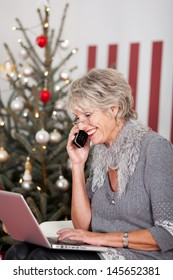 Elderly woman using telephone and her laptop computer on Christmas Eve to wish all her friends a Joyful Christmas, sitting in front of a red and white themed tree