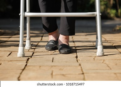 Elderly woman using walker in backyard
