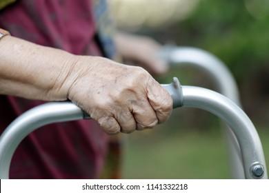 Elderly woman using a walker in backyard