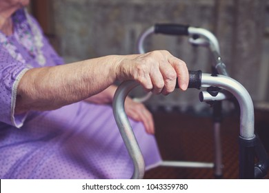 Elderly woman using a walker at home.