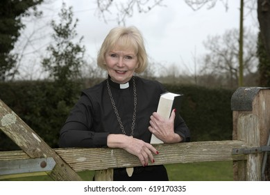 Elderly woman vicar visiting her parish seen leaning on a garden gate