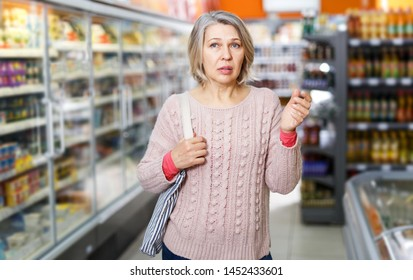 Elderly woman visiting supermarket food department for shopping