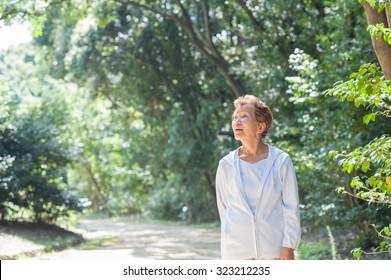An elderly woman walking in the park