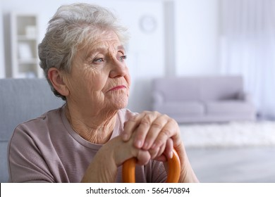 Elderly woman with walking stick at home