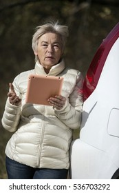 Elderly woman walking with a tablet.