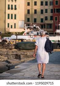elderly woman walks on the pier