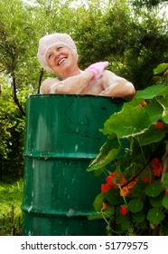 The elderly woman washes in the cask