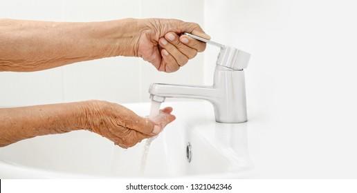 Elderly woman washes hand in bathroom