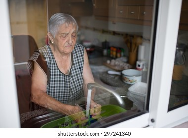 Elderly woman washing dishes in the kitchen