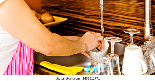 Elderly woman washing dishes in sink. Close view on her hands while cleaning.