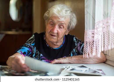 Elderly woman watching photos sitting at table.