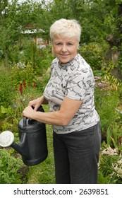 The elderly woman waters a kitchen garden