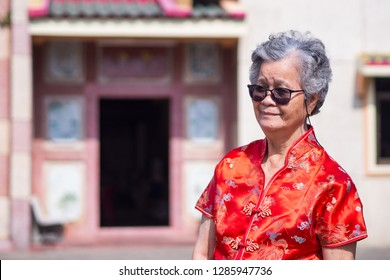 An elderly woman wearing cheongsam red shirt standing at Chinese Temple.