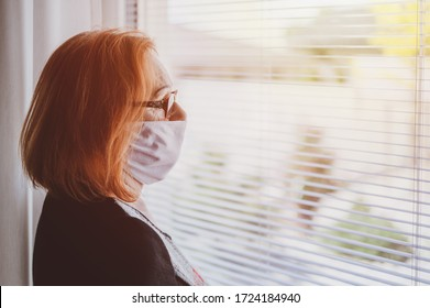 Elderly woman wearing hand made protective face mask, in nursing care home, looking outside window with sadness in her eyes, self isolation due to the global COVID-19 Coronavirus pandemic.
