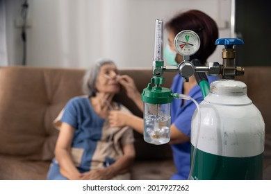 Elderly woman wearing oxygen nasal canula at home.