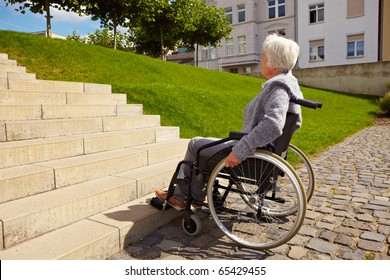 Elderly woman in wheelchair looking at stairs