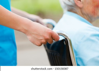 Elderly woman in wheelchair pushed by nurse's hands.