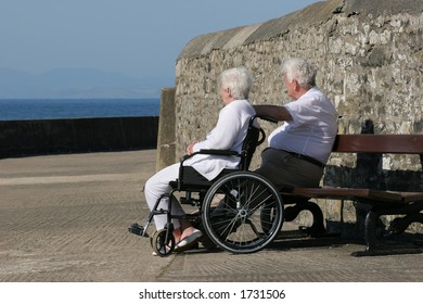 Elderly woman in a wheelchair sitting next to an elderly man, gazing at a sea view.