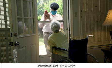 An elderly woman in a wheelchair social distancing because of COVID19 visits with a caring relative or neighbor through her glass storm door.