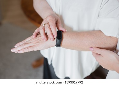 An elderly woman in a white blouse is wearing a fitness bracelet. Smart watch on the hand of an old woman. Pensioner Using Fitness Tracker.