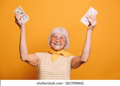 Ältere Frau mit weißem Haar mit T-Shirt, orangefarbener Brille und gelbem Kravat. Frau einzeln auf orangefarbenem Hintergrund. Alte Frau hebt die Hände und hält Geld