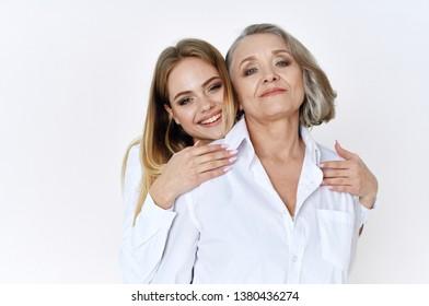 Elderly woman in white shirt next to her granddaughter Family Light background