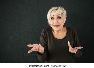 An elderly woman who was deceived, or she does not understand what happened to her, shows by gesture a question mark with her hands