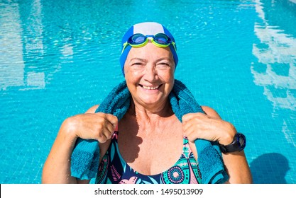 An elderly woman who enjoys the swimming pool. One people with large smile. Blue swimming cap and goggles. Healthy lifestyle by doing physical activity. Sunny day and transparent water