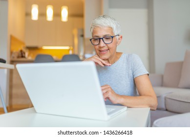Elderly woman working on laptop computer, smiling. Woman Working From Home On Laptop In Modern Apartment. Trendy woman working on laptop from home