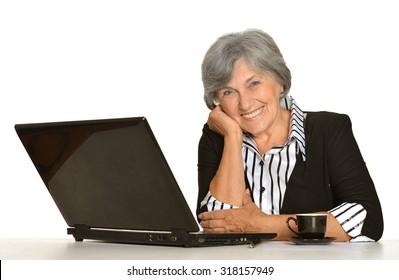 Elderly woman working on laptop on white background
