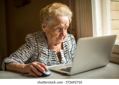 Elderly woman working on laptop at home sitting at the table.