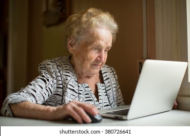 Elderly woman working on laptop sitting near the window.