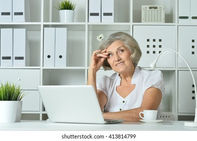 Elderly woman working on laptop
