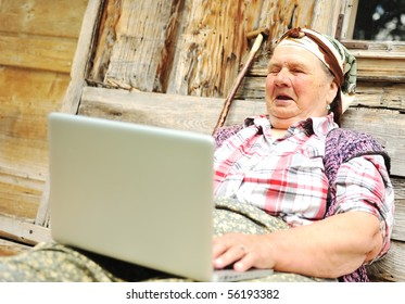 Elderly woman working on laptop in front of wooden house