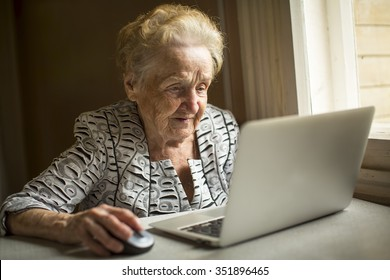 An elderly woman works on a computer.