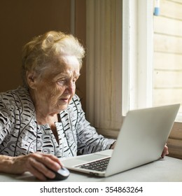 An elderly woman works on a laptop.