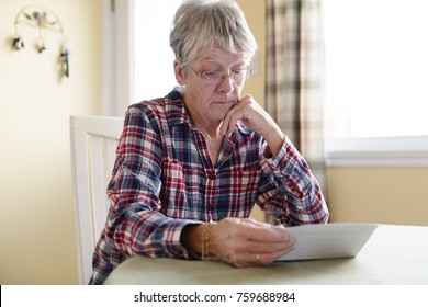 A Elderly woman worry about bill notice at home