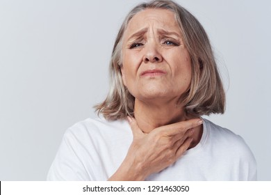 An elderly woman wrinkled her face and holds her hand near the throat, sore throat health problems