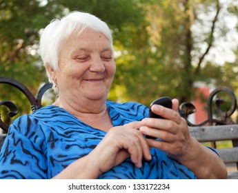 The elderly woman, writes the message in phone