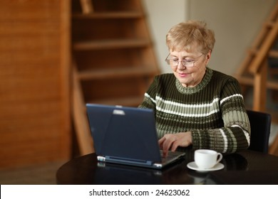 The elderly woman writes  on the computer
