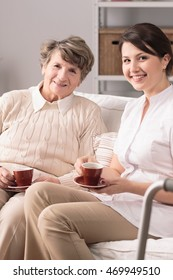 Elderly woman and young female caregiver sitting on couch and drinking tea