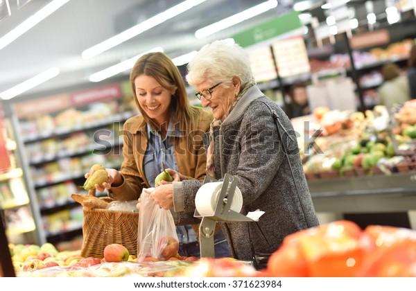 Ältere Frau mit jungen Frauen im Lebensmittelgeschäft