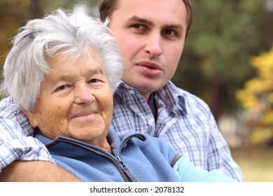 Elderly woman and young man sitting on the bench