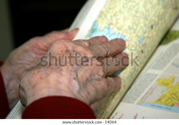 elderly woman's hands holding book