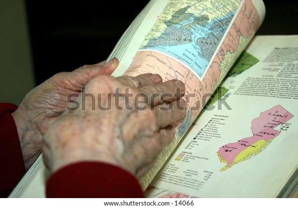 elderly woman's hands holding book