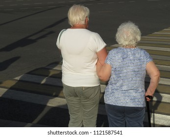 Elderly women cross the street at a pedestrian crossing. Old grey woman with a cane
