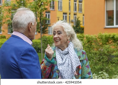 Elderly women emotionally talking to an elderly man. Bright clothes, a festive makeover.